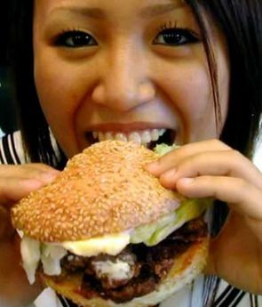 A Japanese bites into a whale burger