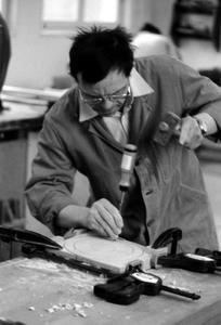 Un compagnon qui place son ciseau à bois pour façonner une roue de trottinette...