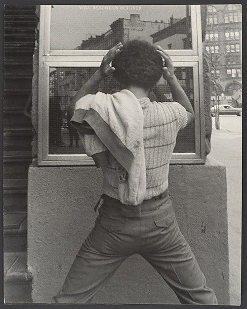 Young-Man-FixingHair-in-Window-New-York-City-1970sLeon-Lev.jpeg