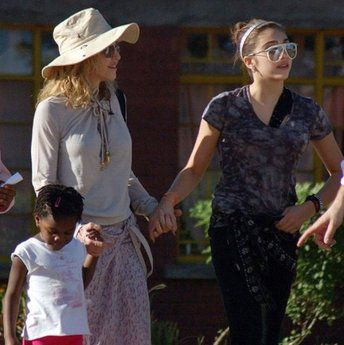Madonna walks with her adopted daughter Mercy James and her biological daughter Lourdes as she visits Mphandula Child Care Centre in Lilongwe, Malawi on April 8, 2010