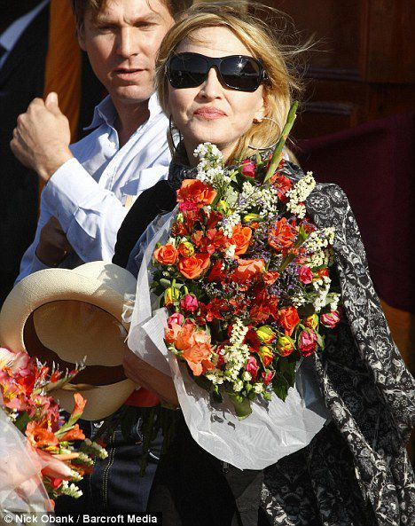 Holding a straw hat and bouquet of flowers, Madonna smiles as she arrives for the launch of the construction of her school in Malawi