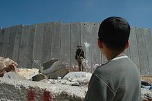 cleach-Boy and soldier in front of Israeli wall