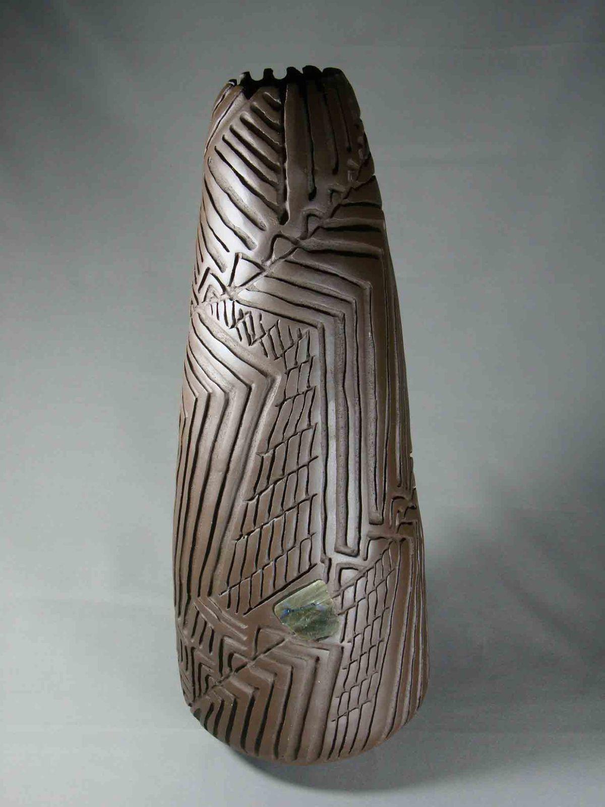 Résonnances, décor cannelé sur grès noir, incustation de pierre ou d'élément naturel.