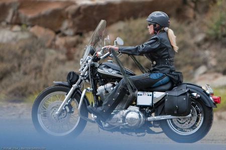 Female motorcycle biker in leathers, blond ponytail, in Morro Bay, CA
