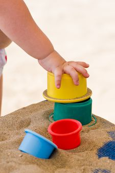Children's hand and toys on sand