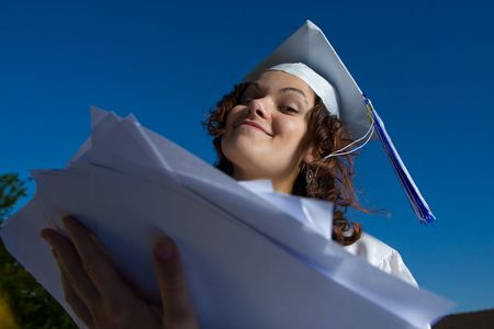 young graduate girl with heap of papers
