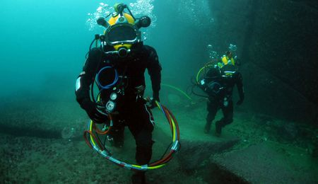 Navy divers assigned to the Chilean Buzo Salvatoaja, walk along the oc