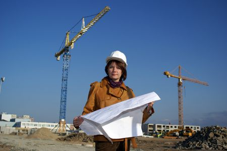 Pretty woman architect holding blueprints