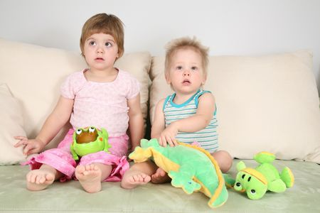 two children on sofa with toys