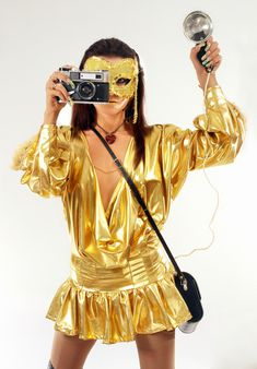 Sexy girl in golden mask & dress with old photo camera.