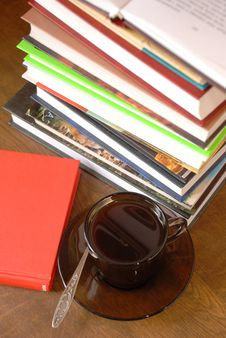 Cup of coffee and a pile of books