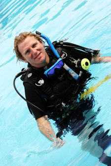 Happy scuba diving instructor in the swimming pool.