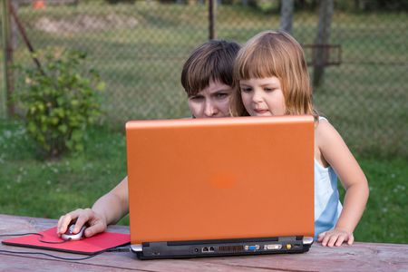 little girl playing computer game with adult woman