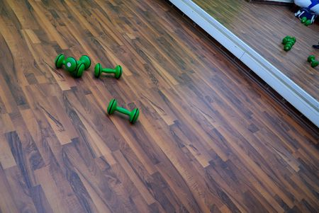 green dumbbells on patquet floor