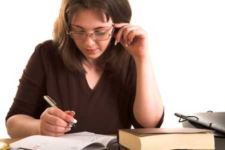 Young woman in glasse writing something in copybook