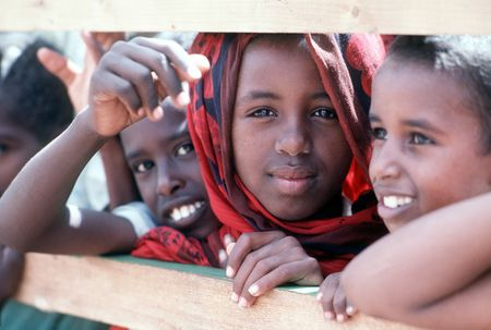 Somali children watch members of Naval Mobile Construction Battalion 1