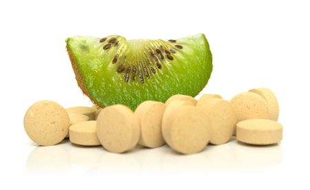 Slice of kiwi on a heap of tablets
