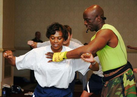 Fitness trainer Billy Blanks shows a female workout participant, the p