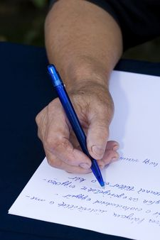 Woman's hand holding a pen writing