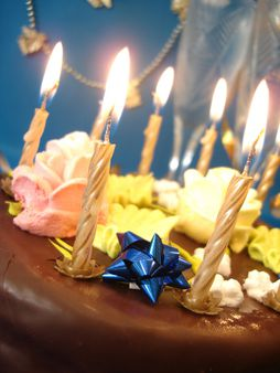 cake and candles, two glasses with champagne on blue