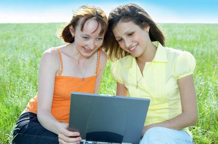 Two beautiful girls with laptop computer