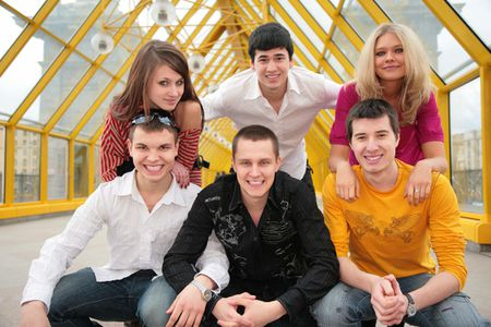 group of young persons pose on footbridge