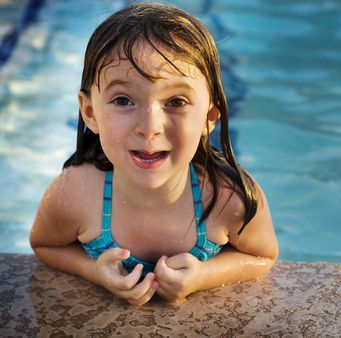 Little girl with pretty smile playing in swimming pool